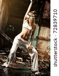 Young woman dancing on industrial background. Contrast colors. - stock photo