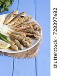 Small photo of Plate of fried fresh fish red mullets serving with seasonal herbs, sliced onion, lemon, arugula and parsley on light blue wood table. Mullus is subtropical marine genus of perciformes fish of family .