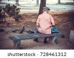 An old man in the park sits on a bench and feeds pigeons