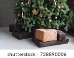 Small photo of Christmas tree with wooden rustic decorations and presents under it in loft interior.