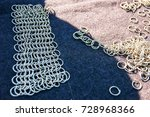 Small photo of Rings for crafting ringmail on the table with the sun