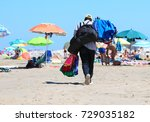 Small photo of African abusive towel and shorts seller in the resort beach