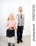 Small photo of Two kids holding stationery, markers for drawing. Children are dressed in school uniform. Boy in a white shirt, trousers, tie and jacket. Girl in a pink golf sweater, black skirt, pantyhose and shoes