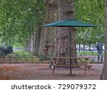 an unoccupied bench and parasol ... | Shutterstock . vector #729079372