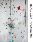 Child Climbing On A High Wall