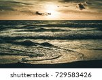 Small photo of rough seas as waves crash on the shore on a dar windy morning during tide change
