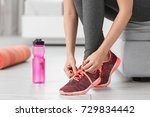 young sporty woman tying... | Shutterstock . vector #729834442