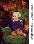 Small photo of little boy sitting near a Christmas tree and a fireplace and waiting for a new yea
