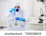 Small photo of Talented virology research scientist wearing coverall and respirator working with biohazard substance while conducting experiment at modern laboratory