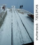 Small photo of Snow-covered cog railway tracks with the silhouette of two people at the tip of Pikes Peak summit on a cold day