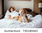 Stock photo woman and her beagle dog meet morning in bed 730180465