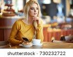 blonde woman drinking coffee in ... | Shutterstock . vector #730232722