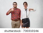 Small photo of Agree and disagree concept. Two male and femae friends express different emotions as evaluate something. Cheerful wonk man raise thumb shows ok sign. Unpleased female model expresses dislike