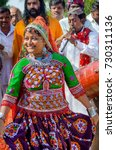 Small photo of KUTCH, GUJARAT, INDIA - 6 NOV. 2014: Young Beautiful Gujarati Kutchi village girl dancing wearing colorful embroidered costume at Rann of Kutch.