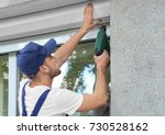 man installing roller shutter... | Shutterstock . vector #730528162