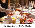 Stock photo hand holding glasses with rose wine over a table rich with balkan and moldovan cuisine dishes 730692496