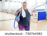 overweight girl in a gym | Shutterstock . vector #730764382