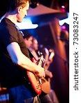 musician plays a guitar at a concert - stock photo