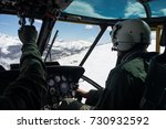Small photo of Military pilot and copilot flying a UH-3H Sea King helicopter over snowed mountains. Andes, Bariloche.