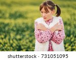 Small photo of Outdoor portrait of pretty 10 year old girl, wearing pink vintage dress and faux fur bodywarmer, posing in a field, arms crossed