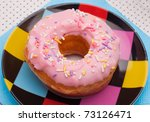 Pink dounut on multicolored plate - stock photo
