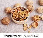 Small photo of Walnut kernels in a wooden bowl and whole walnuts on a table. Walnuts
