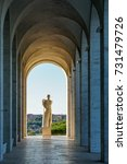 Small photo of A view down a passageway of archways leading to a statue overlooking the Italian countryside.