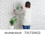 woman putting photo frame on... | Shutterstock . vector #731720422