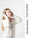 young woman listening to music | Shutterstock . vector #731741992