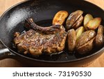 Porkchop with potatoes in pan - stock photo