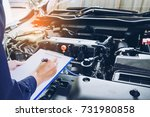 mechanic holding a clipboard of service order working in garage. Repair service. - stock photo