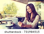 young woman in cafe  using... | Shutterstock . vector #731984515