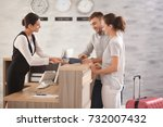 young couple paying for hotel... | Shutterstock . vector #732007432