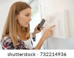 woman programming home security ...   Shutterstock . vector #732214936