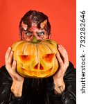 Small photo of Demon with horns and hidden face holds carved jack o lantern. Devil or monster with October decorations. Halloween party concept. Man wearing scary makeup holds pumpkin on red background