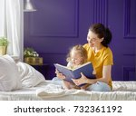 pretty young mother reading a... | Shutterstock . vector #732361192
