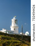 Small photo of Stumble head lighthouse on a sunny day. Pencaer, Pembrokeshire, Wales, United Kingdom.