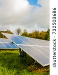 Small photo of Arrangement of solar energy production plant. Solar collectors collect lass autumn sun rays in the field near the village in Germany. Sideview. Ecology, green energy and sustainable development.
