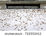 Small photo of a lonely bench in a city park in the middle of a carpet made up of first snow that fell out ahead of time and dry fallen leaves