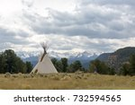 Small photo of Native American Tee Pee campsite sits alone on the grass field under cloudy sky with Sneffels Range in background, Colorado.