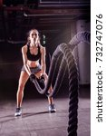 Small photo of Battle ropes session. Attractive young fit and toned sportswoman working out in fitness training gym