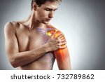 Small photo of Man holding his injured shoulder that's highlighted in red. Medical concept.