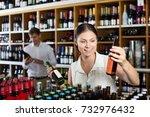 positive woman choosing bottle... | Shutterstock . vector #732976432