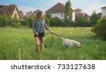 Stock photo young caucasian woman and her big white dog are walking on a field near small houses in summer day 733127638