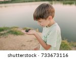 the boy is holding a toad on... | Shutterstock . vector #733673116