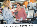 young saleswoman scanning... | Shutterstock . vector #733721326