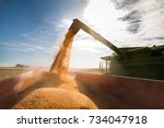 pouring corn grain into tractor ... | Shutterstock . vector #734047918