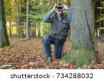 a hunter kneels behind a tree... | Shutterstock . vector #734288032
