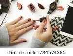 female hands with nail polish... | Shutterstock . vector #734574385