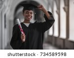 Beautiful young Afro American graduate in academic dress is holding diploma, looking at camera and smiling while standing in university hall